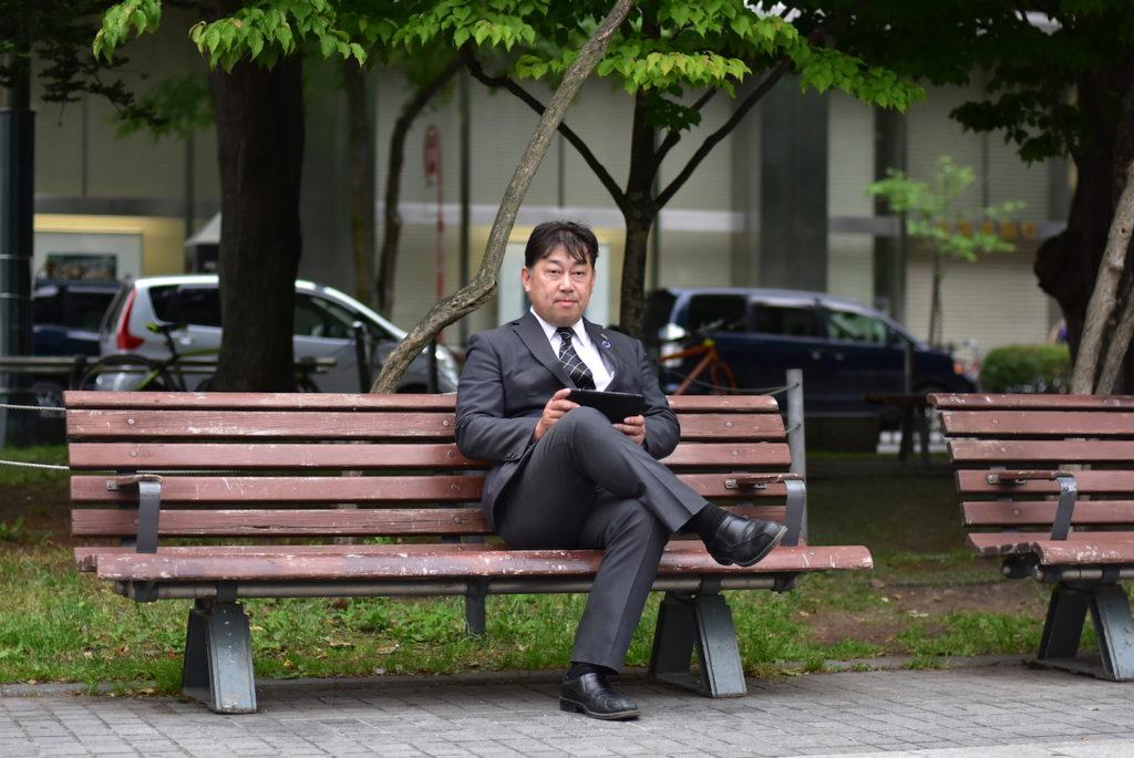 公園のベンチでも仕事をする伊藤常務